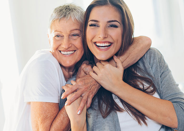 Mature mother and daughter hugging and smiling